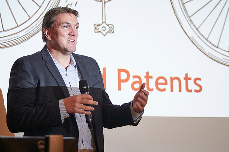 A man in a suit giving a presentation on Patents.