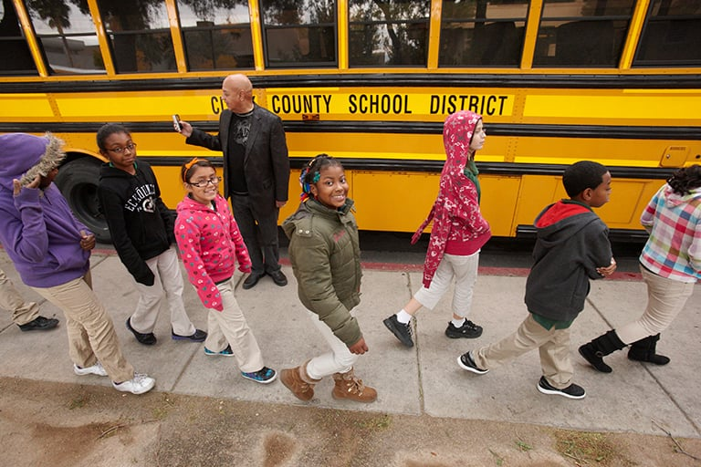 Clark County School District students line up to board a school bus on a field trip.