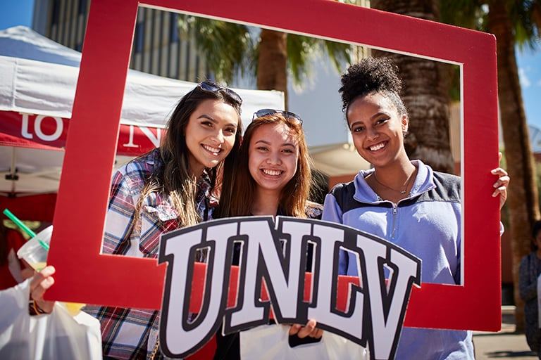 Students on campus posing for a photo inside of a large portable UNLV frame.