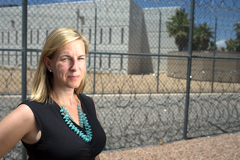 A faculty member standing in front of a prison surrounded by a large fence.