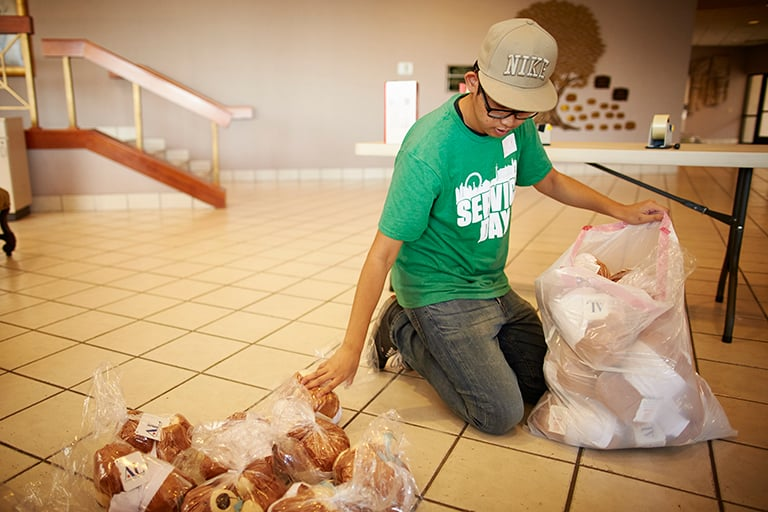 "A student in a green ""service day"" shirt helping nonprofits prepare stuffed animal donations."