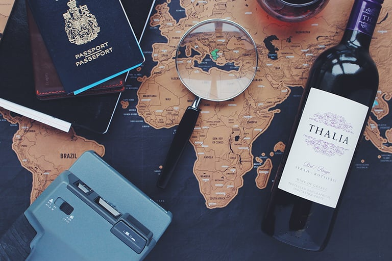 A passport, camera, and bottle of wine on a map with a magnifying glass overlooking it.