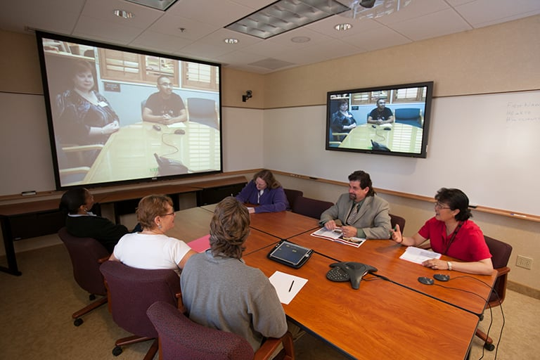 Members of a board having a meeting in a conference room with a projector displaying computer images.