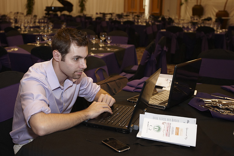 Young male on his laptop during an event