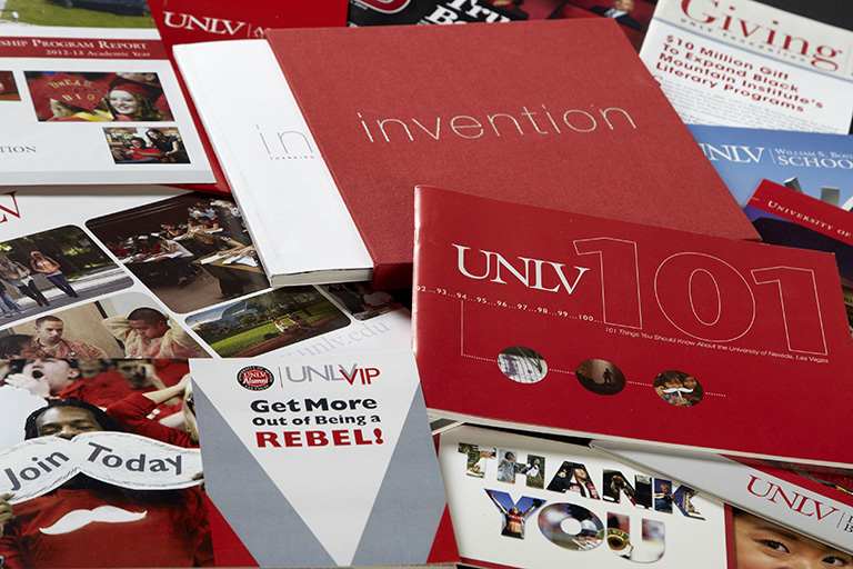U-N-L-V flyers and brochures laid over a table.