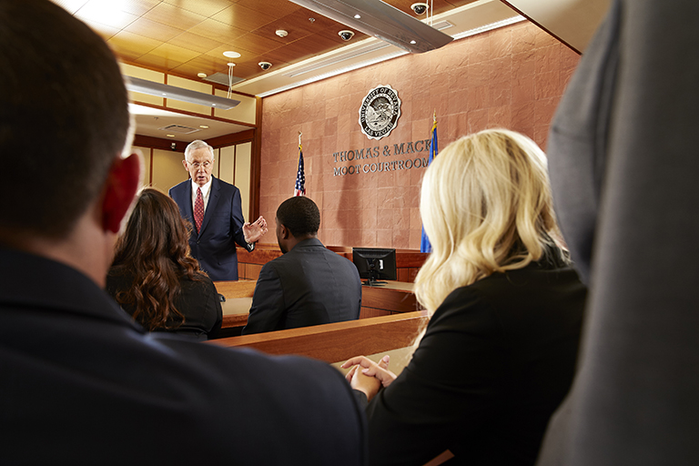 Senator Harry Reid with law students inside the Thomas & Mack Moot Courtroom