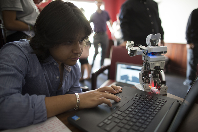 Student focusing on laptop screen accompanied by a small robot.