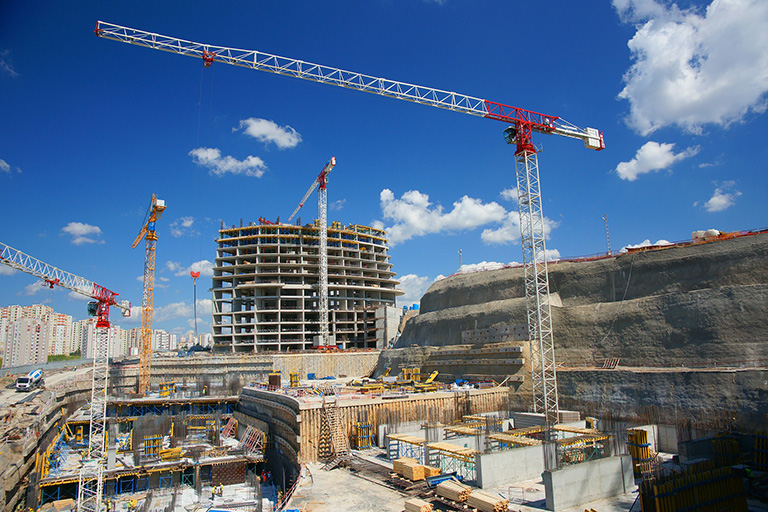 Multiple cranes standing within a construction site.
