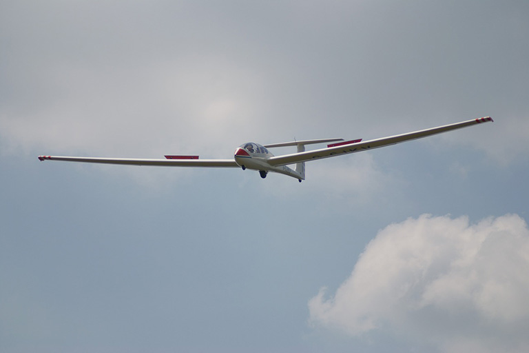 A glider plane flying in mid-air.