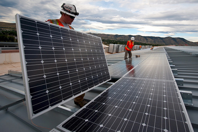 Two workers mounting solar panels