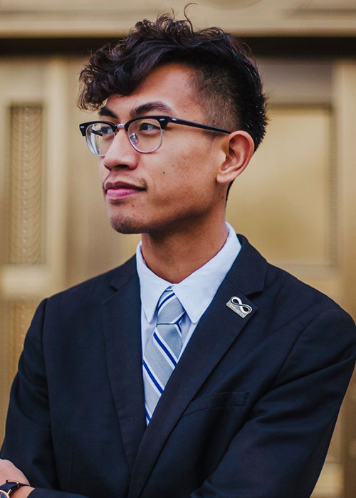 A man with glasses in a navy blue suit.