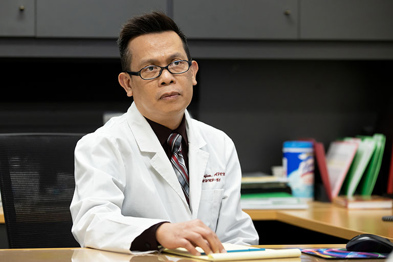 A doctor sitting down at a desk.