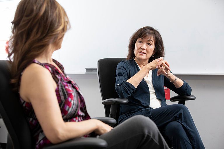Two women sitting down and speaking to each other.
