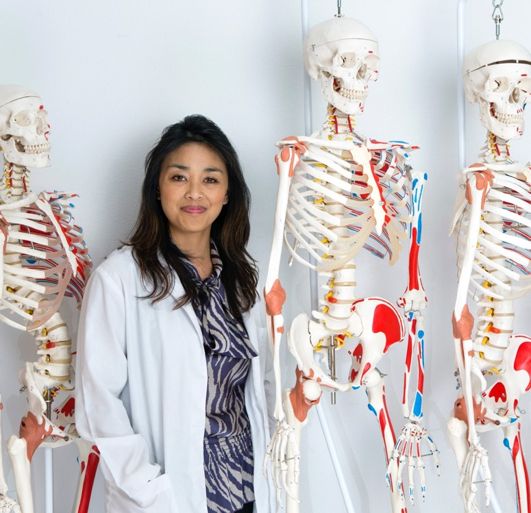 A woman standing in front of model skeletons.