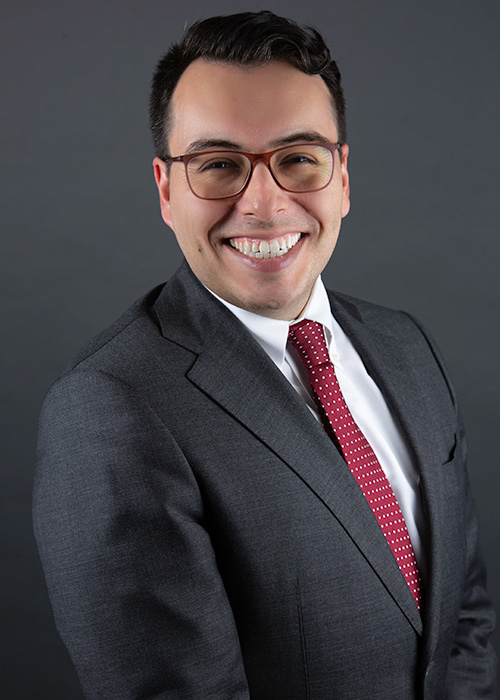 A man with glasses smiling.