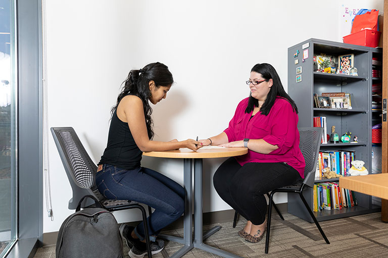 Two women taking notes at a table.