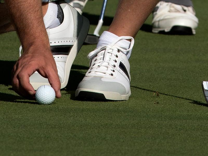 A man positioning a golf ball