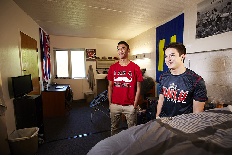 Two male students inside a dorm room.
