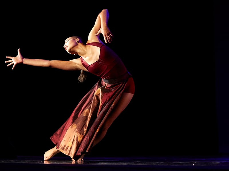 Woman wearing a long burgundy dress striking a dramatic dance pose under dramatic lighting