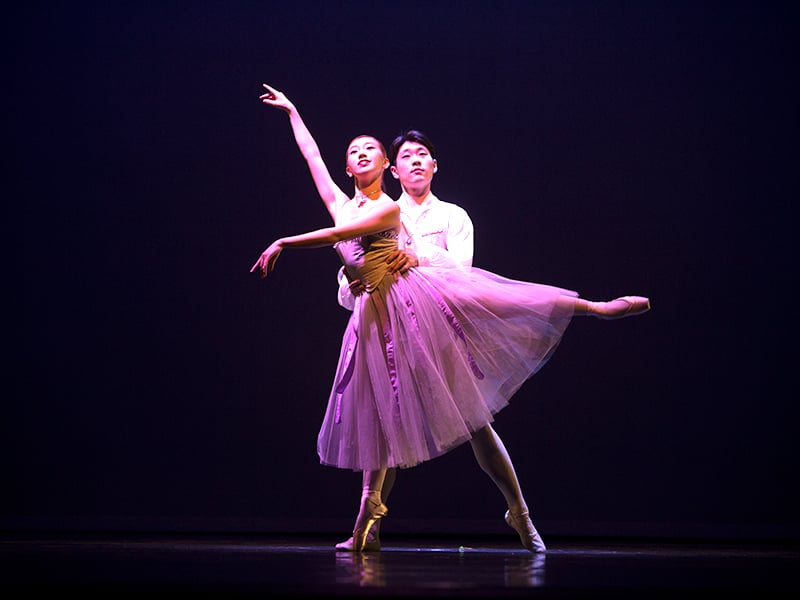 Two ballet dancers on stage performing