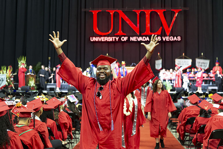 Graduate with arms up in celebration