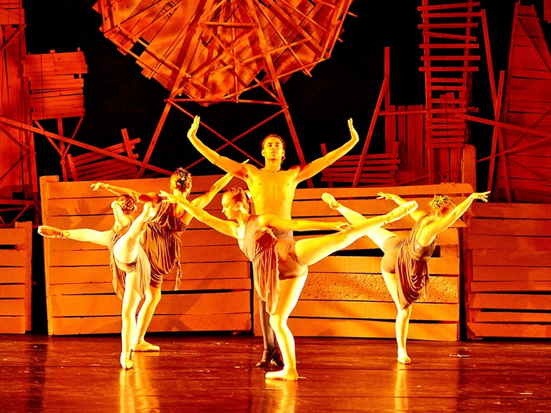 Women dancing around a shirtless man under bright yellow lighting