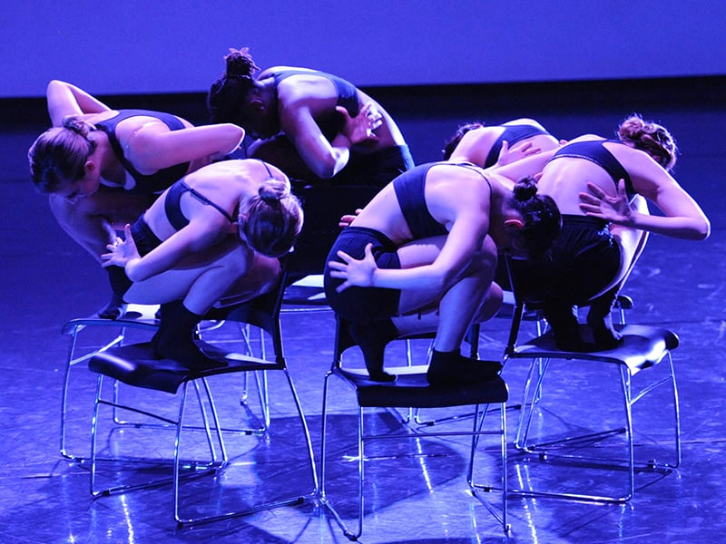 Six women crouching on chairs in a circle formation