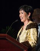 Sue Kim speaking behind a podium