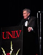 Gary Nelson standing on a UNLV stage wearing a tuxedo