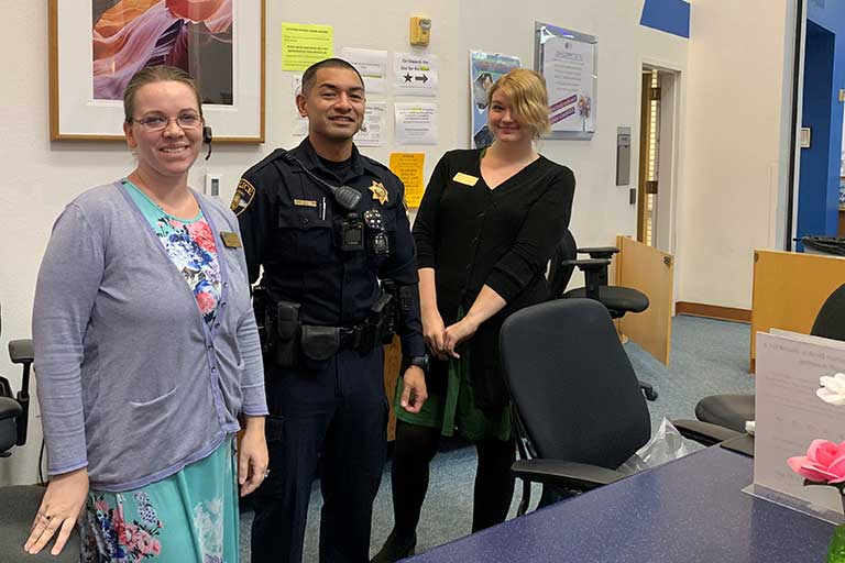 Officer and two faculty members smile