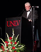 Joe Aldridge in a tuxedo speaking behind a UNLV podium