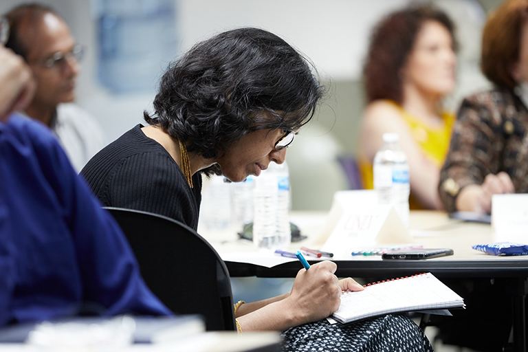 A woman writing on her notebook.
