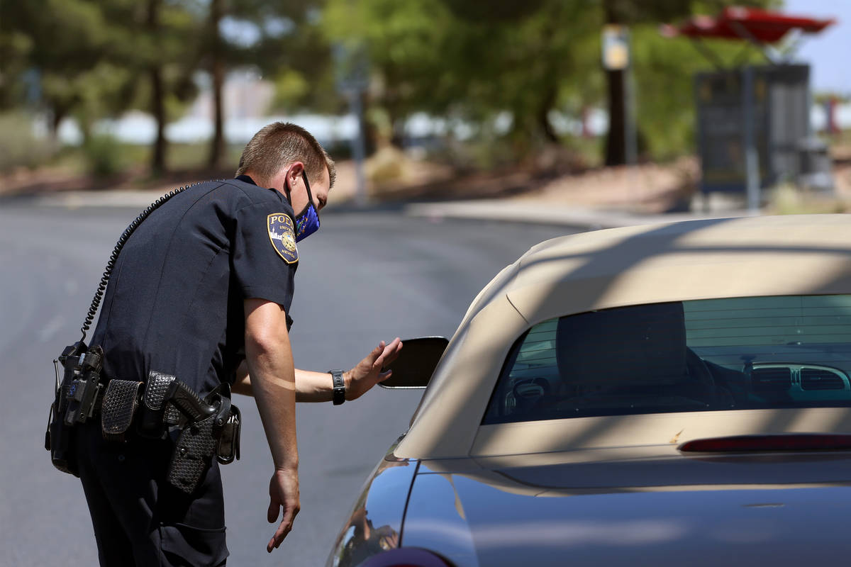 A police officer talking to the driver in the car.