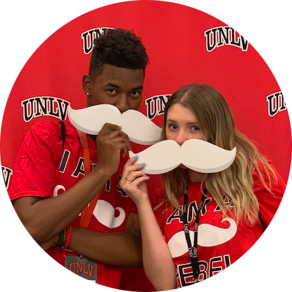 Two students hold mascot mustaches for Rebels Give