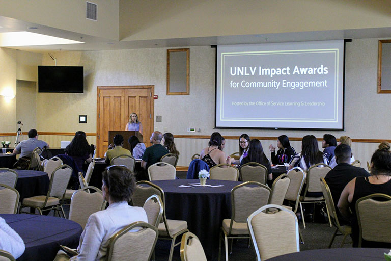 People paying attention to an UNLV Impact Awards presentation