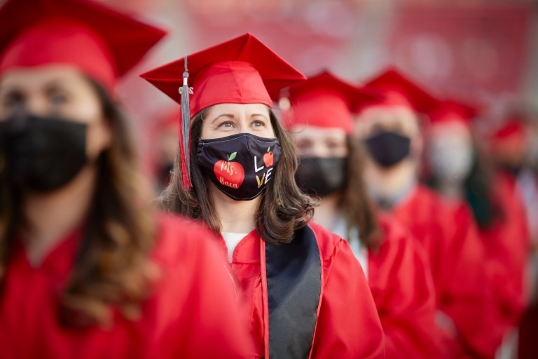 Woman in graduation gown with face mask