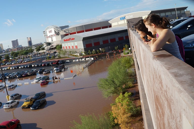 Two students looking down at a flooded parking lot in front of the Thomas and Mack Center.