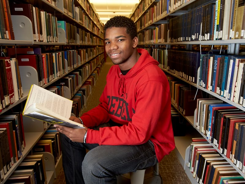 A student sitting in the library, holding an open book.