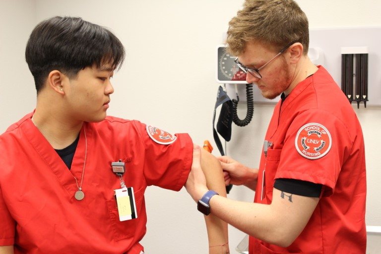 Nursing student hold other students arm
