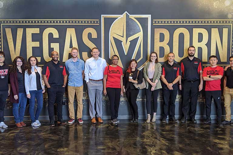 Employee photo with Golden Knights banner