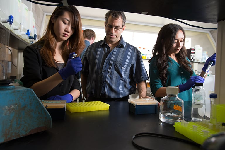 A male professor observing as two female students work in a lab, using droppers.