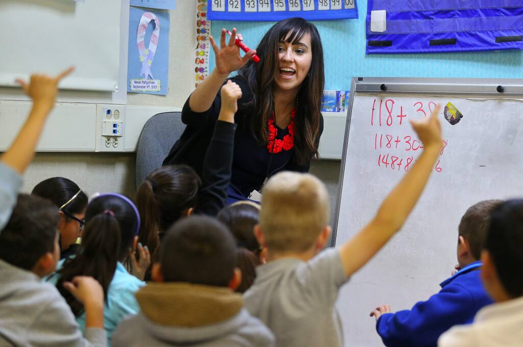 Teacher showing something in front of kids raising hands