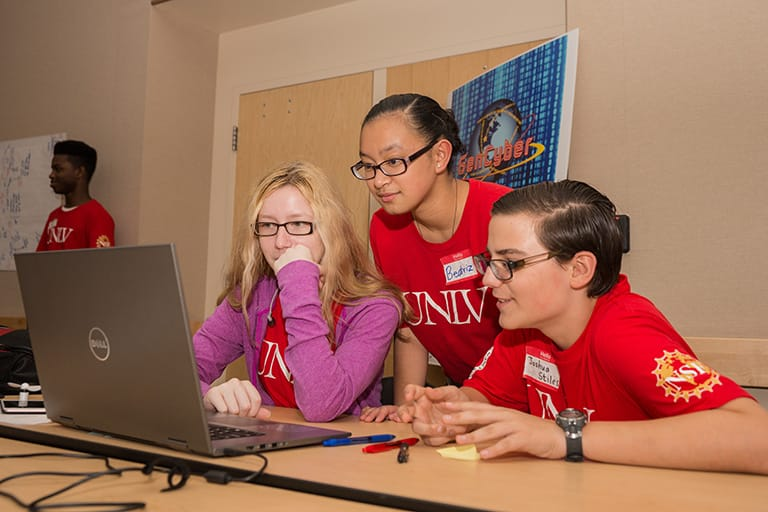 Female students sitting in front of a laptop at GenCyber Summer Camp.
