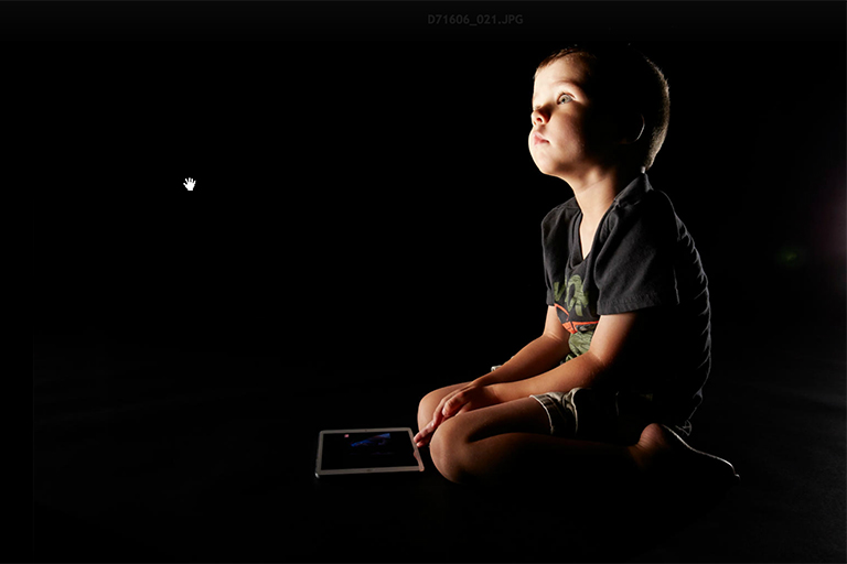 A child with a tablet under a light.