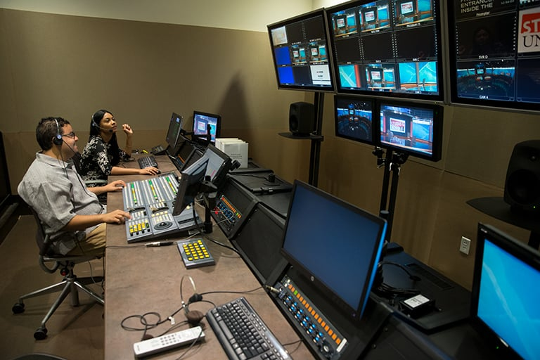 A newsroom backstage with computers and screens overviewing.