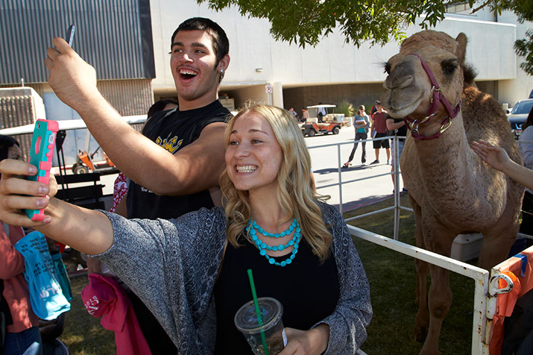 Students taking a selfie with a camel