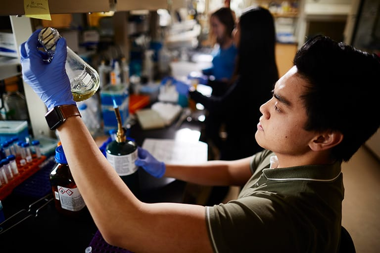 Undergraduate research assistant holding a beaker