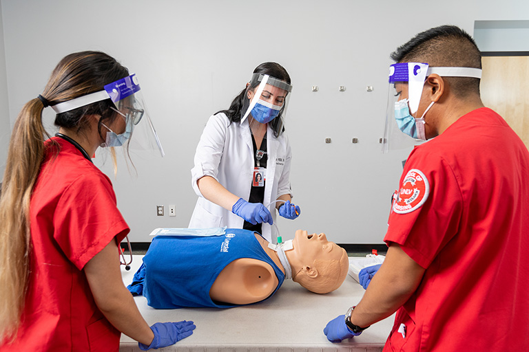 Students practice on a mannequin