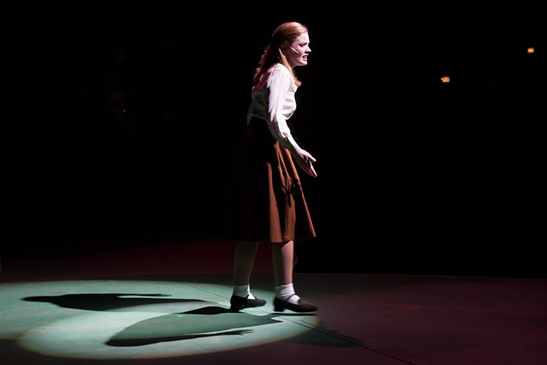 A student on center stage of the theatre.