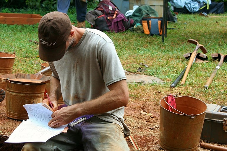 A archeologist writing down some notes at a dig site.